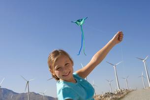 Girl (7-9) with kite on wind farm  portraitの写真素材 [FYI03627863]