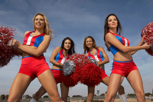 Cheerleaders doing routine with pom poms on football fieldの写真素材 [FYI03627878]