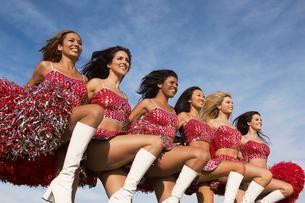 Cheerleaders in a row kicking legsの写真素材 [FYI03627881]