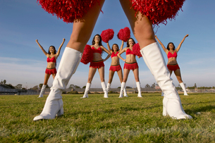 Cheerleader in white knee high boots  low section with cheの写真素材 [FYI03627885]