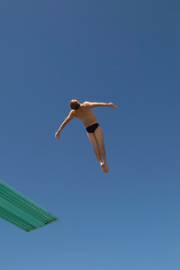 Man diving from diving board  mid airの写真素材 [FYI03627887]