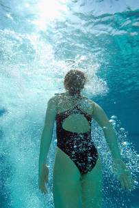 Woman coming up for air in pool  back viewの写真素材 [FYI03627893]