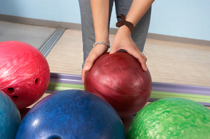 Young woman selecting bowling ball  mid sectionの写真素材 [FYI03627907]