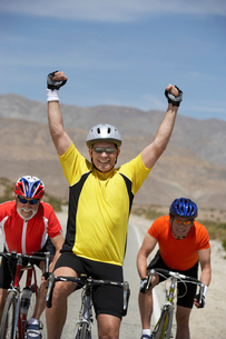 Cyclist cheering with raised arms  portraitの写真素材 [FYI03627916]