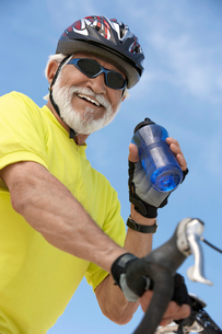 Cyclist drinking from bottle of water  portrait  low angleの写真素材 [FYI03627917]