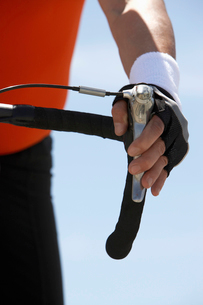 Man with hand on bicycle brake  close-up on handの写真素材 [FYI03627927]