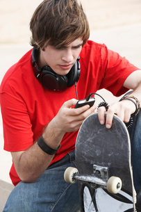 Young skateboarder using MP3 Player outsideの写真素材 [FYI03627937]
