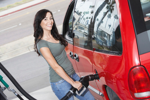 Young woman filling car with gas at gas station  elevatedの写真素材 [FYI03627939]