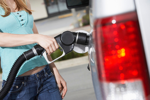 Young woman filling car with gas at gas station  mid sectiの写真素材 [FYI03627940]
