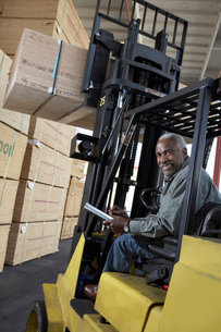 Man using forklift to lift box in warehouseの写真素材 [FYI03627952]