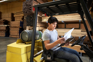 Man sitting in forklift reading paperwork in warehouseの写真素材 [FYI03627957]