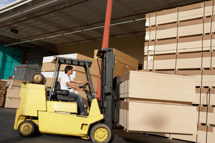Side view of male worker operating forklift vehicleの写真素材 [FYI03627966]