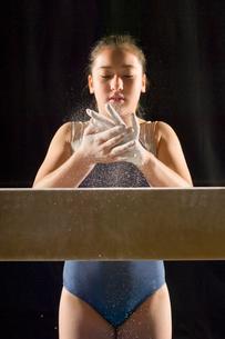 Gymnast (13-15) rubbing chalk into hands  portraitの写真素材 [FYI03627974]