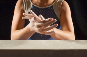Gymnast (13-15) rubbing chalk into hands  mid sectionの写真素材 [FYI03627975]