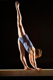 Gymnast (13-15) striking pose on balance beamの写真素材 [FYI03627977]