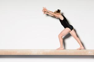 Gymnast(13-15)  on balance beam preparing to do handstandの写真素材 [FYI03627979]