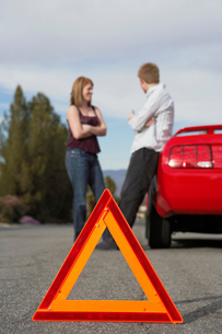 Two motorists standing by broken down car with warning triの写真素材 [FYI03628011]