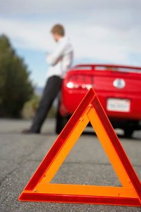 Warning triangle standing by man leaning on broken down caの写真素材 [FYI03628013]