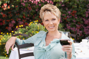 Elegant mature woman sitting in garden  holding wine glassの写真素材 [FYI03628023]