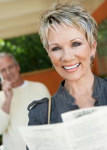 Elegant mature woman holding brochureの写真素材 [FYI03628025]