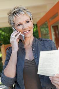 Elegant mature woman using mobile phone holding brochureの写真素材 [FYI03628028]
