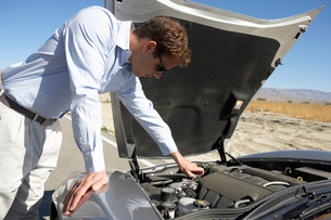 Man looking at engine of sports car by side of desert roadの写真素材 [FYI03628034]