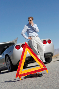 Warning triangle in front of man on cell phone by sports cの写真素材 [FYI03628035]