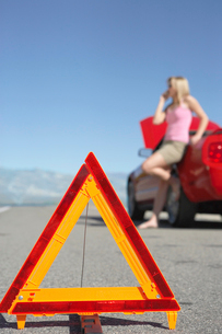 Warning triangle in front of woman on cell phone by red spの写真素材 [FYI03628040]