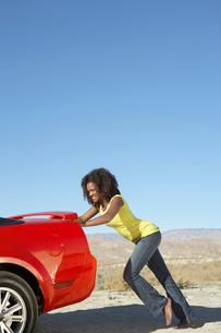 Women pushing broken down sports car on desert roadの写真素材 [FYI03628043]