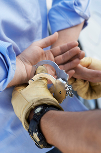 Police officer handcuffing man  close up on handsの写真素材 [FYI03628053]