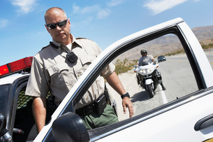 Two police officers stopping on side of desert roadの写真素材 [FYI03628057]