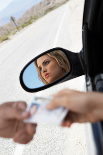 Woman sitting in car handing diving licence to police offiの写真素材 [FYI03628062]