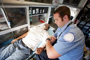 Man receiving medical aid inside ambulanceの写真素材 [FYI03628068]