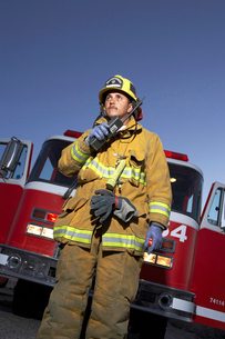 Fire fighter using two way radio in front of fire engineの写真素材 [FYI03628069]
