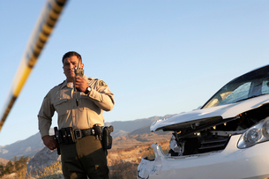 Police officer using walkie-talkie next to wrecked carの写真素材 [FYI03628071]