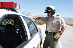 Police officer standing by police car on desert highwayの写真素材 [FYI03628073]