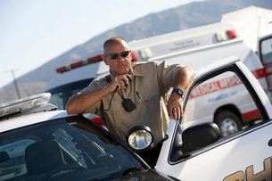 Police officer using two-way radio by police carの写真素材 [FYI03628075]