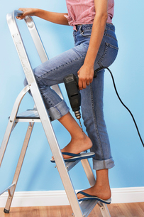 Woman holding power drill on stepladder  low sectionの写真素材 [FYI03628095]