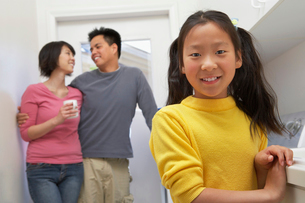 Family with daughter (7-9) in laundry roomの写真素材 [FYI03628110]