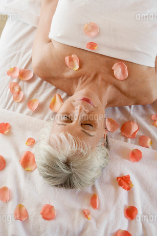 Woman at spa with rose petals around  head and shouldersの写真素材 [FYI03628130]