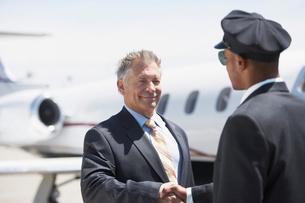 Businessman Beside private jet shaking hands with pilotの写真素材 [FYI03628164]