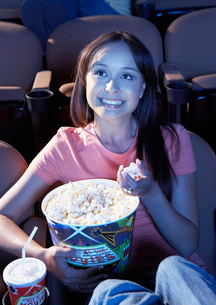 Smiling young woman Eating Popcorn  watching movie in Theaの写真素材 [FYI03628169]