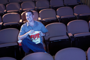 Man sitting alone in empty theatre eating popcorn  Watchinの写真素材 [FYI03628174]
