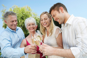 Young couple and older couple Toasting with Champagne outsの写真素材 [FYI03628180]