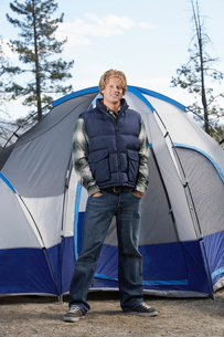 Young Man in warm clothing standing in front of tent.の写真素材 [FYI03628200]