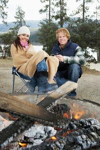 Young couple in warm clothing  sitting by campfireの写真素材 [FYI03628210]