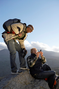 Two young men using compass at top of hillの写真素材 [FYI03628230]