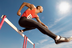 Male athlete jumping hurdle  mid airの写真素材 [FYI03628240]