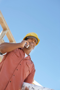 Man on building site on cell phone  half lengthの写真素材 [FYI03628242]