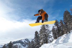 Male snowboarder jumping over snow covered hill  mid airの写真素材 [FYI03628263]